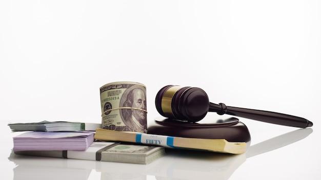 Молоток судьи и пачки банкнот долларов и евро на белом фоне