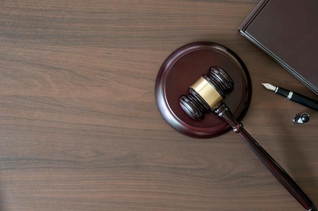 판사의 망치, 책, 나무 배경에 펜, 위쪽 전망. 법률 개념