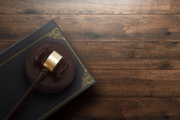 Judge's gavel and book on wooden background