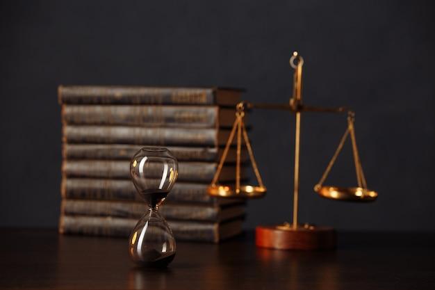 裁判官のガベル、本、正義の鱗、木製のテーブルの砂時計。