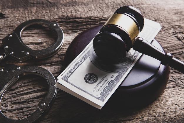 Судейский молоток, деньги и наручники на столе. пробный