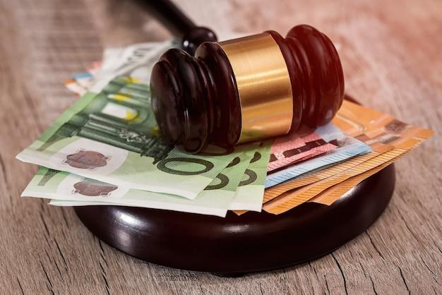 Молоток судьи на стопке банкнот евро