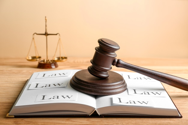 Judge's gavel and open book on wooden table