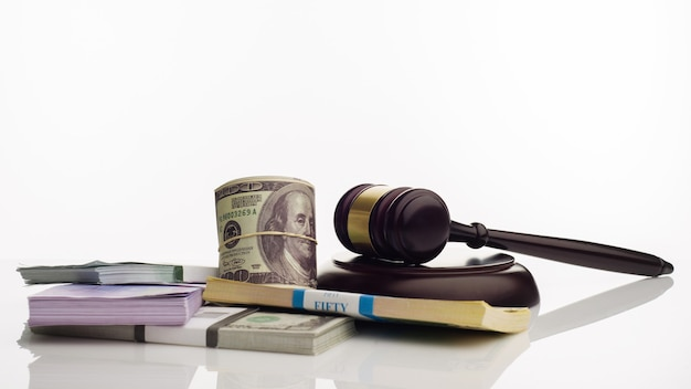 Judge's gavel and packs of dollars and euro banknotes on a white background