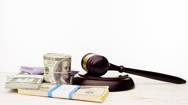 Judge's gavel and packs of dollars and euro banknotes on a white wooden table.