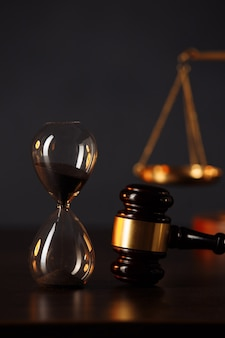 Judge's gavel, scales of justice and hourglass on wooden table.