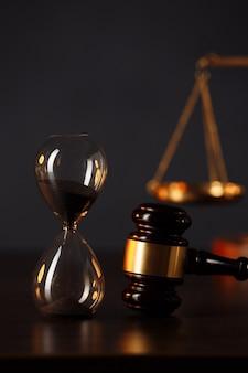 裁判官のガベル、正義の鱗、木製のテーブルの砂時計。
