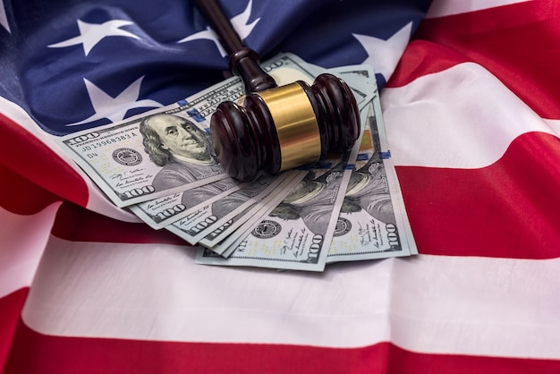 Judge's gavel with dollar banknotes on american flag