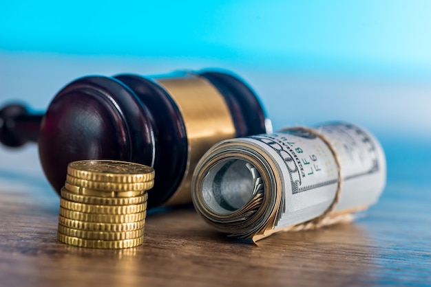 Молоток судьи с долларами в рулоне и золотыми монетами