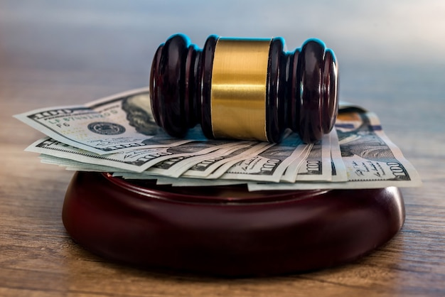 Judge's gavel with dollars in roll and golden coins