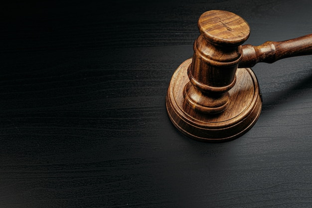 Judge's gavel on wooden table in dark