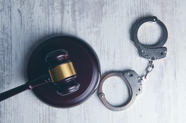 テーブルの上の裁判官のハンマーと手錠