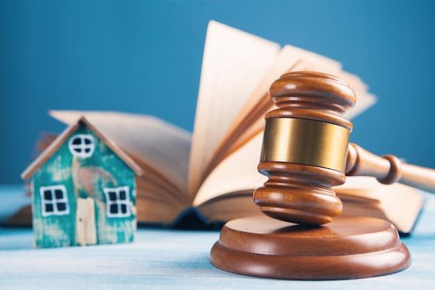 裁判官のハンマー、本、テーブルの上の家