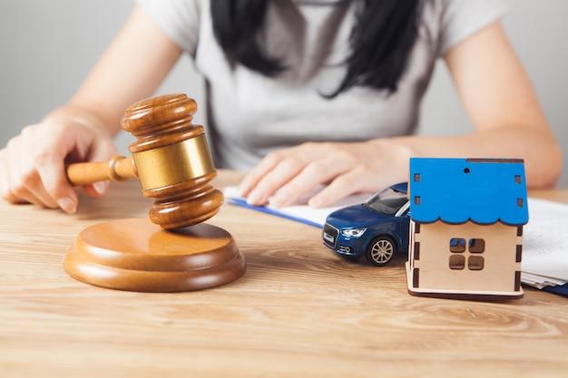 裁判官のハンマー、車、テーブルの上の家