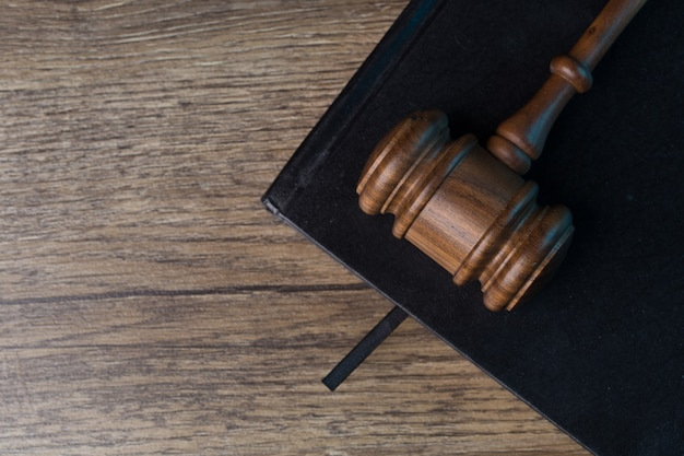 Judge's hammer lies on black notebook at desk