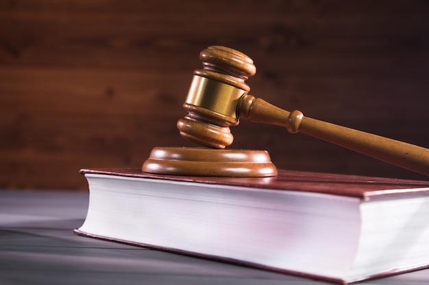 木製のテーブルの上の本の裁判官のハンマー