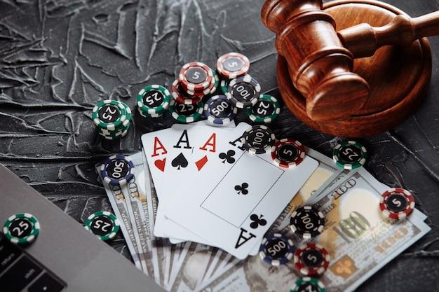 裁判官の木製のガベル、ポーカーチップ、お金、トランプ。法の概念とギャンブルの規制。