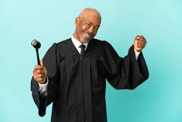Judge senior man isolated on blue background doing strong gesture