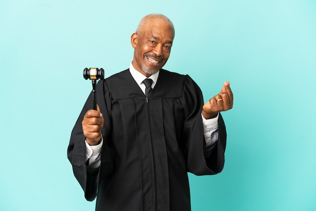 Judge senior man isolated on blue background making money gesture
