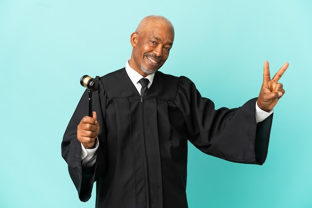 Judge senior man isolated on blue background smiling and showing victory sign