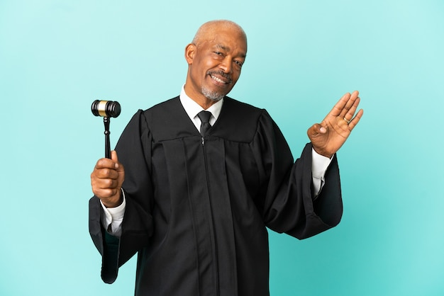 Judge senior man isolated on blue surface saluting with hand with happy expression