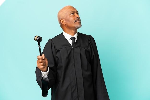 青い背景に孤立し、見上げる年配の男性裁判官