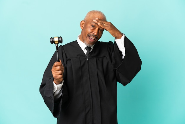 Судья старший мужчина изолирован на синем фоне делает неожиданный жест, глядя в сторону