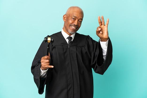 幸せで、指で3つを数えて青い背景に分離された年配の男性裁判官