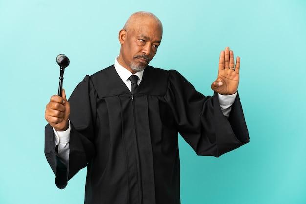 青い背景に孤立した裁判官の年配の男性が停止ジェスチャーをして失望した