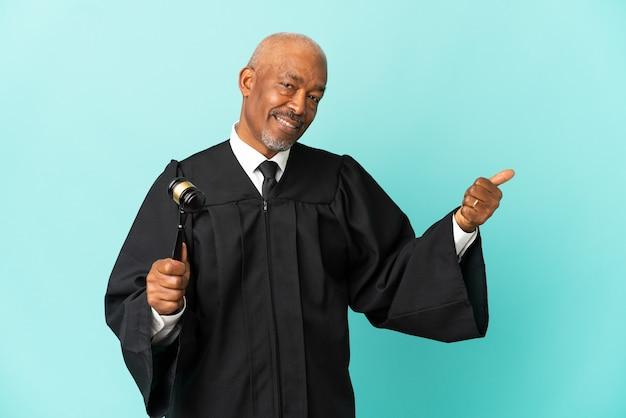제품을 제시하기 위해 측면을 가리키는 파란색 배경에 고립 된 판사 수석 남자