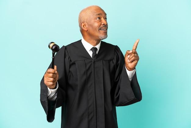 Судья старший мужчина изолирован на синем фоне, думая об идее, указывая пальцем вверх