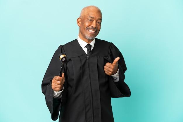 제스처를 엄지 손가락을주는 파란색 벽에 고립 된 판사 수석 남자
