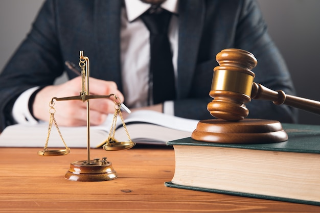 The judge takes notes and on the table scales and a hammer on a gray surface