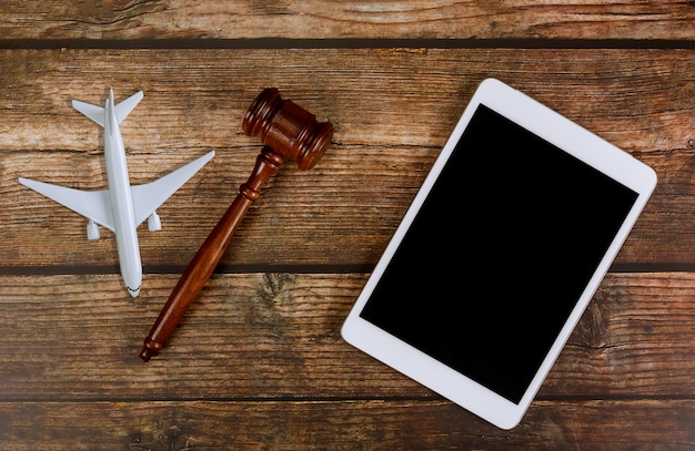 Judge traveling concept planning airplane on wooden judges gavel with digital tablet in airplane model plane