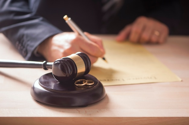 결혼 반지와 함께 테이블에 망치로 판사. 이혼 개념