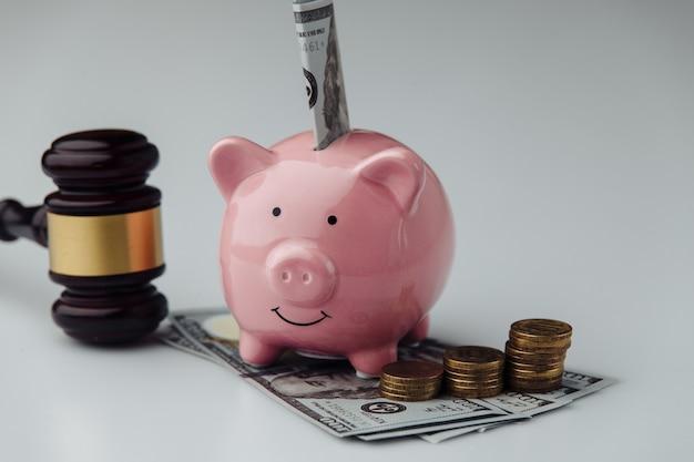 Судья деревянный молоток и копилка с долларовой купюрой на белом столе