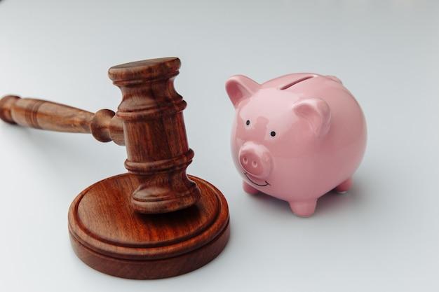 Судья деревянный молоток и розовая копилка на белом.