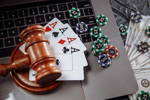 木製のガベル、お金の紙幣、コンピューターのキーボードのトランプ、オンラインギャンブルの概念に関する法的規則を判断します。
