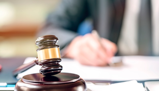 Judge wooden gavel on sounding block on the teble.