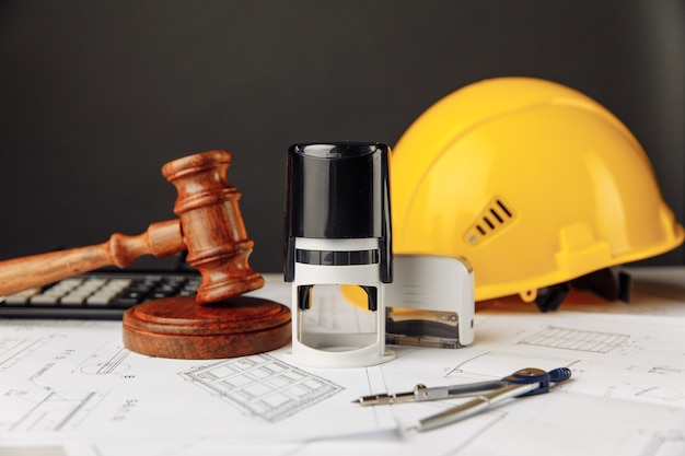Judge wooden gavel stamp and yellow helmet construction plan concept