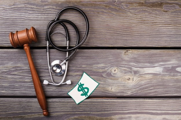 Judgement and healthcare concept. wooden gavel and stethoscope on wooden desk.
