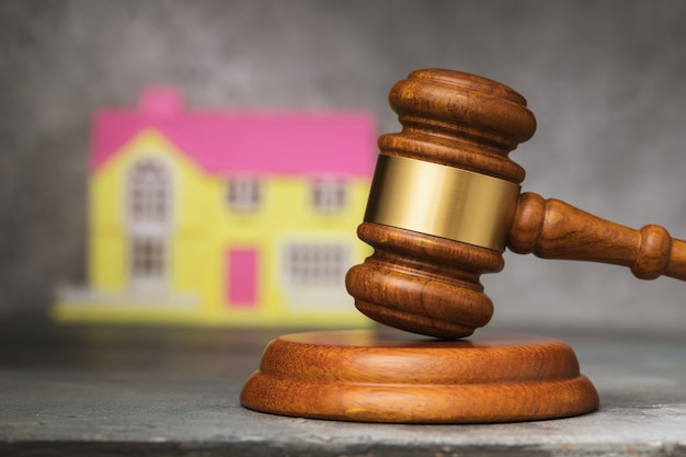 裁判官のガベルと家のクローズアップオークションで不動産を販売するという概念
