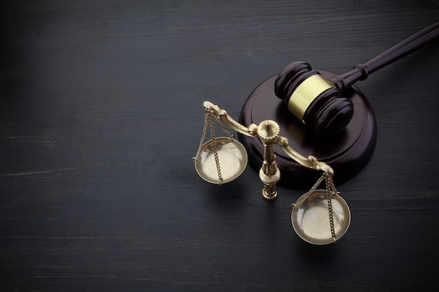 Судьи молоток и весы правосудия на черном столе