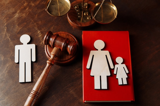 Judges gavel divide family wooden figures. family law book and divorce