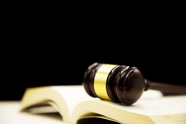책과 나무 테이블에 판사 망치입니다. 법과 정의 개념 배경입니다.