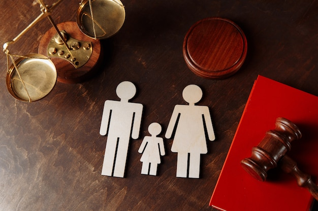 Judges gavel on a red book and family figures