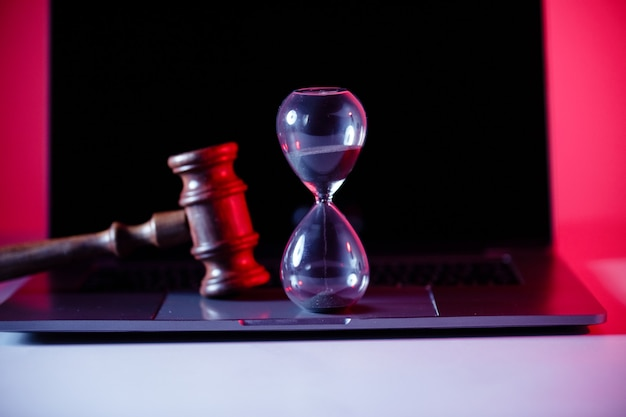 Judges gavel, scales of justice and hourglass on laptop.