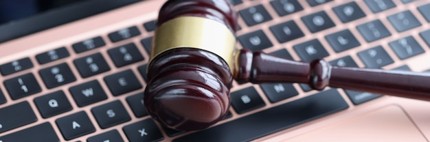 Judges hammer lying on laptop keyboard in courthouse closeup. online auction concept