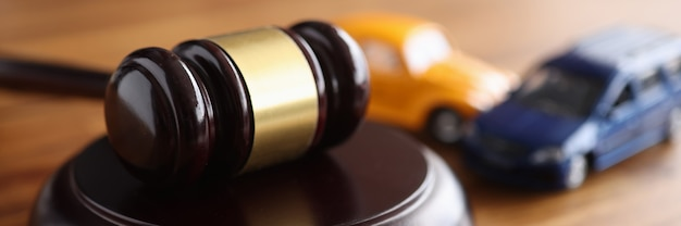 Judges wooden gavel lying on table near toy machines closeup. judicial liability of drivers concept