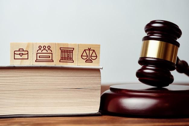 Судебный молоток рядом с книгой и иконами тюрьмы, присяжных и весов.
